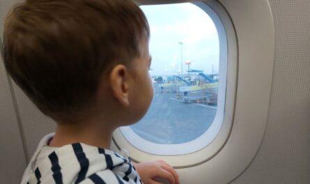 Een kind kijkt door het vliegtuigraam